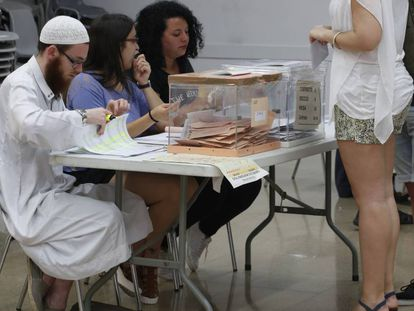 David Franco Portolés checks ID cards at a polling station.