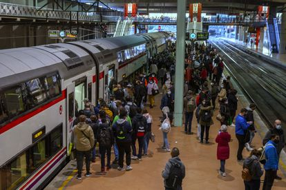Dozens of people wait at a platform at Atocha train station in Madrid on Monday.