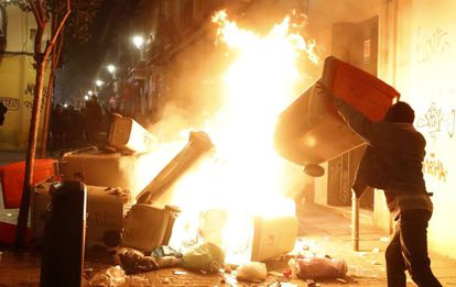 A man sets a trash bin on fire in Calle Mesón de Paredes.