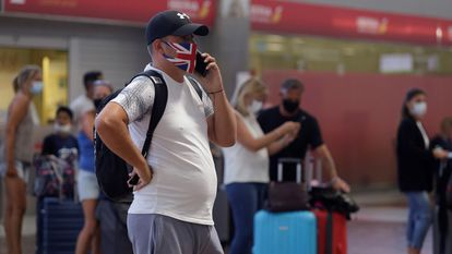 Travelers on a flight to the United Kingdom line up to check in their baggage at Tenerife Sur airport on Sunday.
