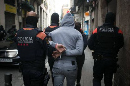 Police take away one of the suspects in El Raval.
