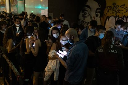 Employees of Sala Apolo in Barcelona check Covid passes outside the club.