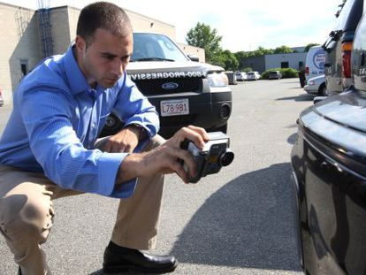 An insurance investigator inspects a car.