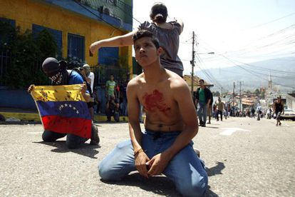 A boy with blood on his chest kneels in front of police after a student died during a protest in San Cristóbal.