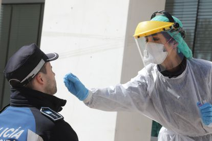 A health worker tests a police officer for the coronavirus in Madrid.