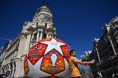 A passerby takes a selfie with a giant replica of the UEFA Champions League ball displayed in Madrid on May 29, 2019 ahead of the final football match between Liverpool and Tottenham Hotspur on June 1. (Photo by GABRIEL BOUYS / AFP)