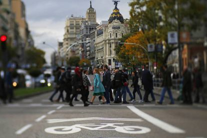 Pedestrians cross Gran Vía avenue, which is part of the Madrid Central zone.