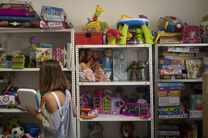 This young girl is keeping donated toys neatly stashed on shelves at a volunteer center in El Paso, La Palma.