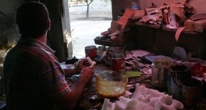 A worker glues shoes together in an illegal workshop in his home.