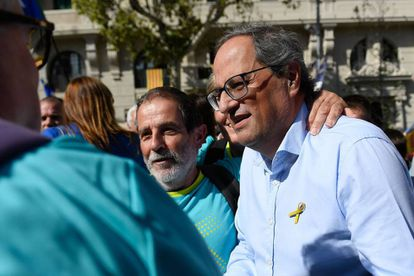 Catalan regional president Quim Torra (R) greets people upon his arrival to the march.