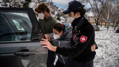 Volunteers Miguel and Rodrigo helping Triana into a car before driving her to La Paz hospital in Madrid.