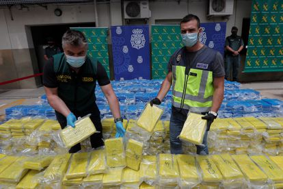 A member of UDYCO (right) and UCO (left) with 3,800 kilos of cocaine seized at the port of Valencia in a joint operation between the National Police and the Civil Guard.