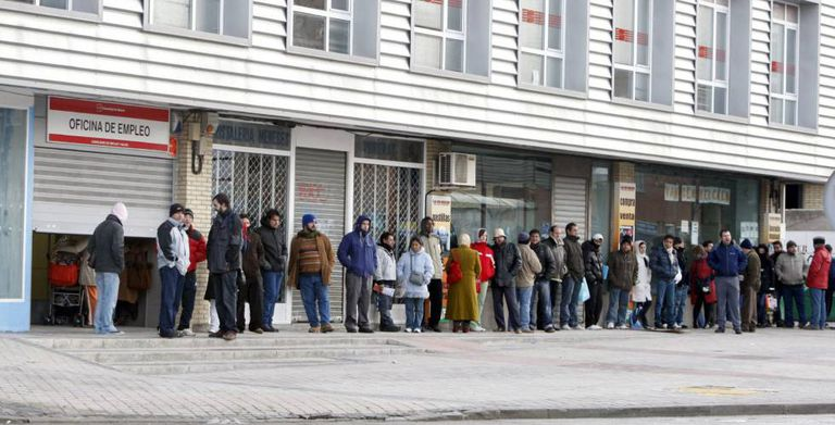 Spaniards wait in line outside a job center.