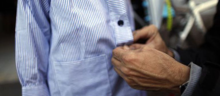 A father buttons up his son's smock before taking him to school in Madrid.