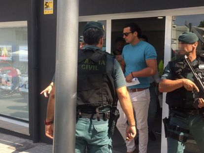 The Civil Guard escorts the owner of the real estate agency after his arrest.