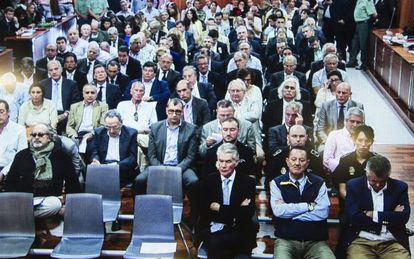 A photograph taken of a monitor screen outside the Málaga courtroom as the defendants prepared to hear the sentence. Former Marbella Mayor Julián Muñoz is second from the right in the front row, next to Juan Antonio Roca (head bowed),