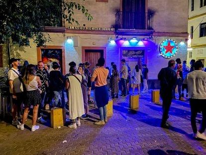 People wait in line outside a nightclub in Seville.