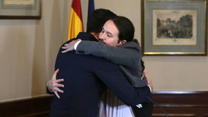 Pedro Sánchez and Pablo Iglesias embrace after signing the deal.
