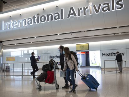 Passengers wearing face masks arrive at London's Heathrow Airport on June 8.