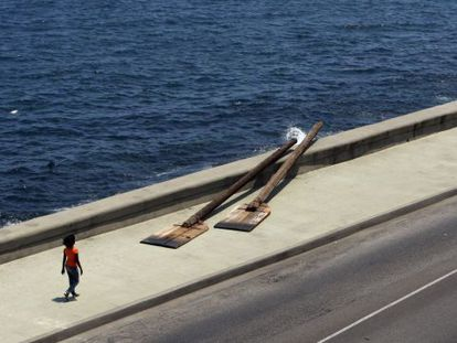 A woman walks along Havana's famous Malecón, where an artist set up two gigantic rowing paddles on the wall.