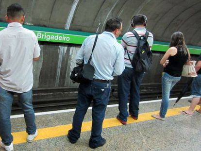 Male passengers eye two girls on the São Paulo metro system.