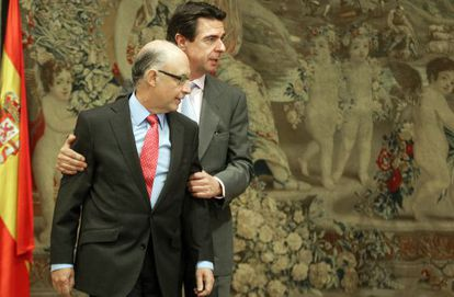 Finance Minister Montoro is grasped by Industry and Energy's Soria.
