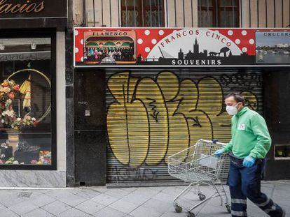 A man walks past closed stores during the coronavirus lockdown in Spain.