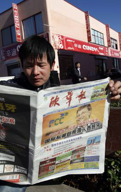 A worker in a Fuenlabrada industrial park reads a Chinese newspaper.