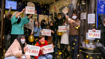 """Workers at Madrid's famous """"Doña Manolita"""" lottery sales agency celebrating the fact that they sold 'décimos' from this year's first and third prizes."""