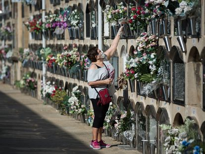 A woman leaves flowers at the Poblenou cemetery in Barcelona.