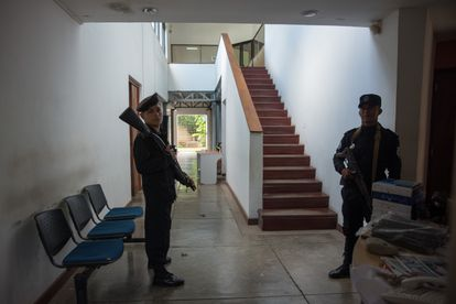Two police officers guard the entrance to the offices of the newspaper 'Confidencial' on December 15, 2018.
