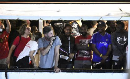 Migrants stand on the 'Open Arms' rescue ship before disembarking at Lampedusa.