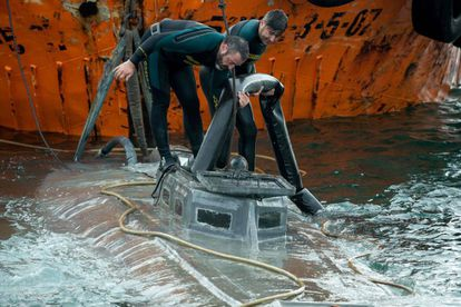 Spanish Civil Guard divers stand over the refloated prow of the submersible.
