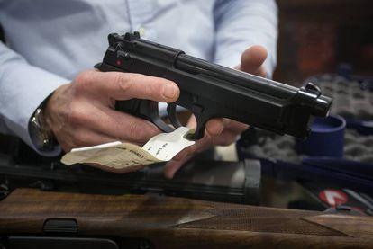 Gun-seller Carlos López handles a pistol.