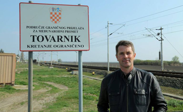Dubravko Blaskovic, president of the regional council of Vukovar, stands by a symbolic sign in Tovarnik, several meters from the Serbian border.