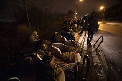 Migrants sleep on the street outside the immigration office.