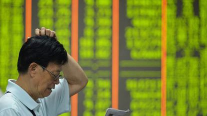 An investor reads in front of a board of share prices in China. Falls are shown in green.