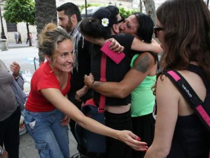 Members of La Utopía community kiss and hug each other after receiving keys to new homes on Wednesday in Seville.