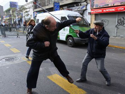 A Pinochet supporter is attacked by a demonstrator Sunday in Santiago.