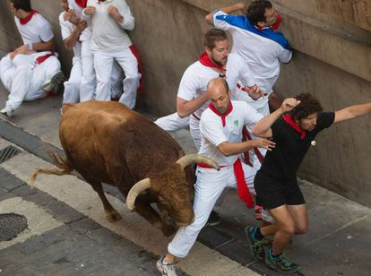 Runners try to move out of the way at the fifth day of the Running of the Bulls in San Fermín.