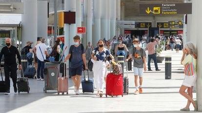 Tourists arrive at Palma de Mallorca airport on July 1.
