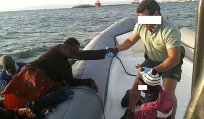 A Civil Guard officer helps a migrant aboard a patrol boat in Spanish waters.