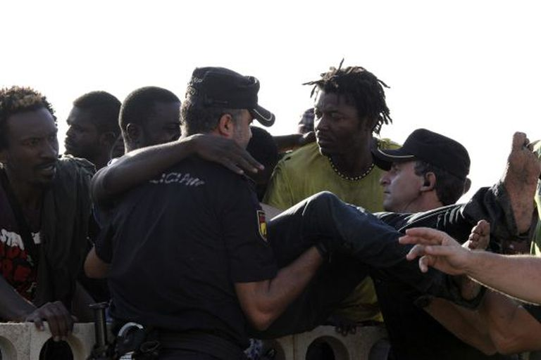 Police grappling with immigrants on Ceuta's beach after a mass attempt to swim onto Spanish soil.