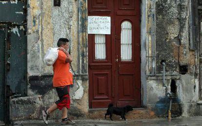 A man walking past a home up for sale in Havana, Cuba.