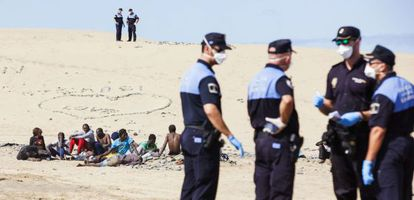 A group of masked police officers watch the immigrants on Maspalomas beach.