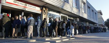 People standing in line outside a Madrid employment office.