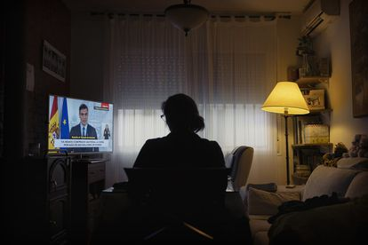 A woman watches Spanish Prime Minister Pedro Sánchez announce an extension to the state of alarm on March 28 and the freezing of all non-essential activity.