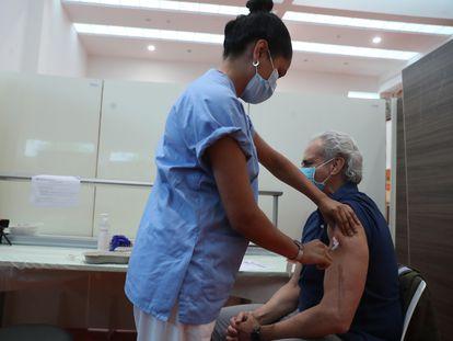 A nurse vaccinates Madrid's health chief Enrique Ruiz Escudero at Puerta de Hierro hospital in Majadahonda.