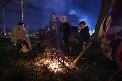 A group of residents gathers around a fire in an open field following a series of earthquakes.