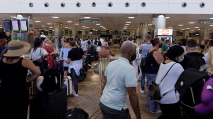 Passengers waiting to check into a flight to the UK in Tenerife a day after the quarantine announcement.
